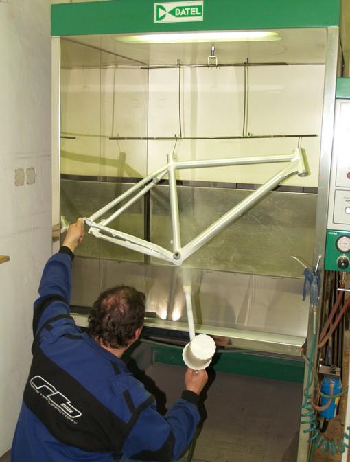 Na rám s ochrannou vrstvou titanu se nanáší elektrostaticky, díky plastové trubičce na pistoli, prášková barva, která se pak vypaluje v peci.