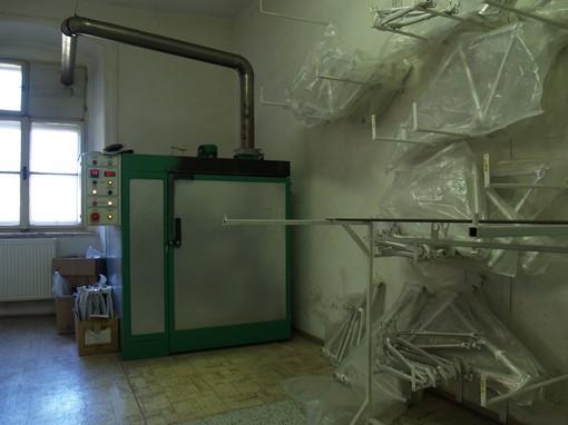 Nalakované rámy končí v peci, kde se prášek spéká a vypaluje do finální podoby.