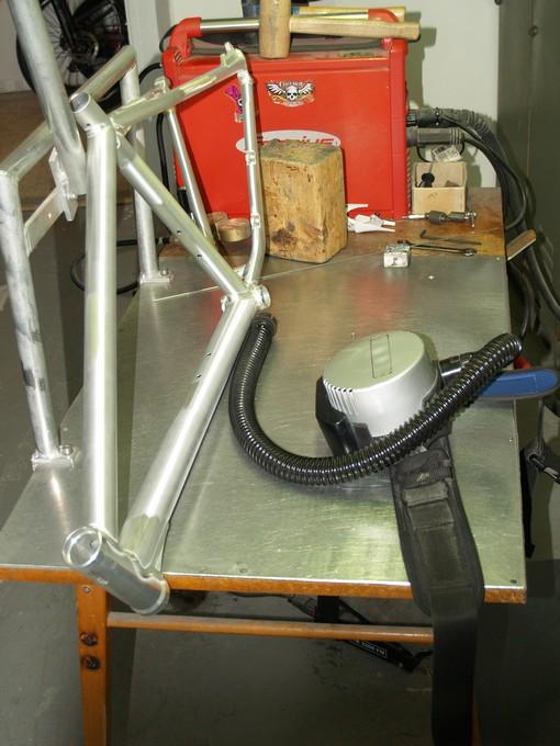 Rám po svaření putuje na titanování kvůli zamezení korozi hliníku pod lakem. Hadice s ventilátorem na snímku přivádí vzduch pod masku svářeče.